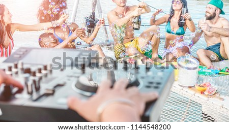 Happy friends drinking champagne in summer boat party - Young millennials people having fun drinking together with dj mixing music - Youth lifestyle and vacation concept - Focus on right guys #1144548200