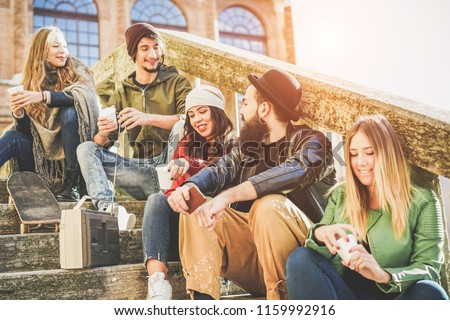 Happy friends drinking coffee take away and laughing in old downtown city center - Young people having fun together - Millennial, youth lifestyle and z generation concept - Focus on bearded man face