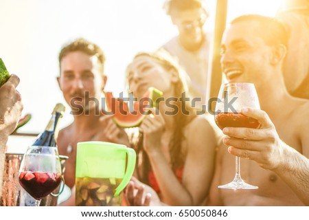 Happy friends drinking sangria wine and eating watermelon at boat party - Young people having fun in summer vacation - Exclusive vacation , friendship , travel concept - Focus on right man hand glass #650050846