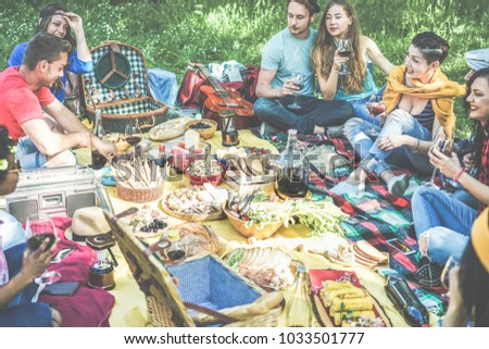 Happy friends eating and drinking wine at picnic outdoor - Young trendy people having fun in nature dining and laughing together  - Main focus on girl with yellow jumper on shoulder