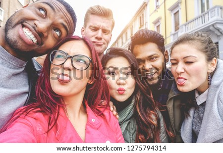Happy friends from diverse cultures and races taking selfie making funny faces - Youth, millennial generation and friendship concept with young people having fun together - Main focus on left girl #1275794314