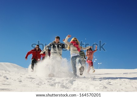 happy friends group  have fun at winter on fresh snow, healthy young people outdoor