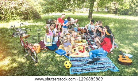 Happy friends group having fun outdoor cheering at bbq picnic with snacks food drinking red wine - Young people enjoying spring time together at barbecue garden party - Youth milennials concept