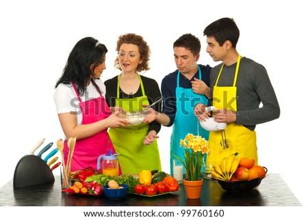 Happy friends having conversation and cooking together in kitchen