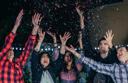 Happy friends having fun among the party confetti