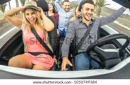 Happy friends having fun and dancing in convertible car in vacation - Young people making party in a cabrio auto during their road trip - Friendship, travel, youth lifestyle concept