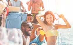 Happy friends having fun at boat party at sunset - Young people laughing and drinking in exclusive tropical sea tour - Youth lifestyle, travel and summer vacation concept - Focus on girl face