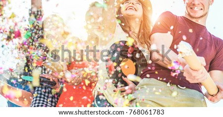 Happy friends having fun at festival party throwing confetti and dancing together - Young people celebrating music fest outdoor - Friendship, hang out and youth concept - Main focus on two right faces #768061783
