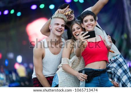Happy friends having fun at music festival #1065713474