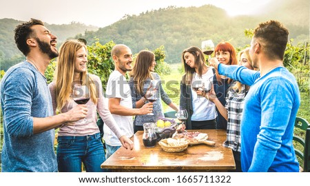 Happy friends having fun drinking red wine in vineyard - Milenial people enjoying harvest time together at countryside farm house - Youth friendship concept on warm filter with sunset sunshine halo
