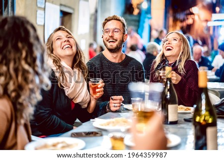 Happy friends having fun drinking white wine at street food festival - Young people eating local plate at restaurant reopening together - Travel and dinning life style concept on light neon filter