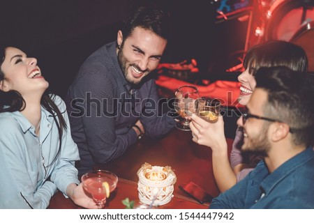 Happy friends having fun in cocktail jazz bar - Young millennial people drinking ad laughing together in nightclub - Nightlife entertainment and youth culture lifestyle holidays concept #1544447942