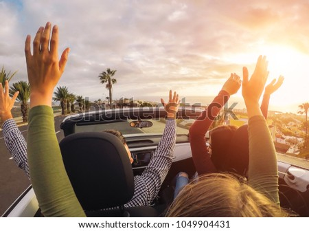 Happy friends having fun in convertible car at sunset in vacation - Young people making party and dancing in a cabrio auto during their road trip - Friendship, travel, youth lifestyle concept #1049904431