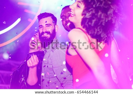 Happy friends having fun in night club with canon ball throwing confetti - Young people enjoying weekend nightlife with original laser lights color - Soft focus on men faces - Warm filter