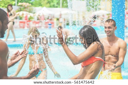 Happy friends having fun in water aqua park on summer vacation - Young multi ethnic couples playing in swimming pool - Friendship and holidays concept - Focus on right girl - Warm cinematic filter