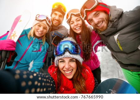 happy friends having fun on winter hodays. Snowbarders and skiers group team friendship making selfie
