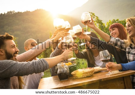 Happy friends having fun outdoor - Young people enjoying harvest time together outside at farm house vineyard countryside - Youth friendship concept - Hands toasting red wine glass at winery on sunset #486675022