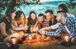 Happy friends having fun with fire sparkles - Young people millennials camping at picnic after sunset - Young people enjoying wine at summer barbecue party - Youth friendship concept on night mood