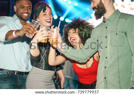 Happy friends having party in club at night - Young people having fun cheering with cocktails at disco dance floor - Youth, nightlife and friendship concept - Soft focus on two left guys