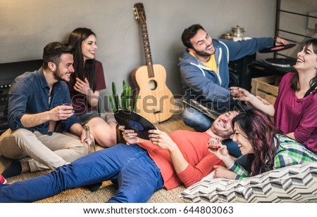 Happy friends having party listening vintage vinyl disc albums in hostel room - Young people having fun drinking shots and laughing together - Soft focus on right bottom woman face - Warm retro filter #644803063