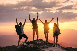 Happy friends hikers or tourists stands with raised arms on mountain top against mountains and looking at sunset