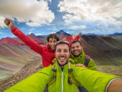 happy friends hikers takes photo selfie in Vinicunca, Peru with background of Rainbow Mountain (5200 m) in Andes, Cordillera de los Andes, Cusco region in South America with cloudy sky