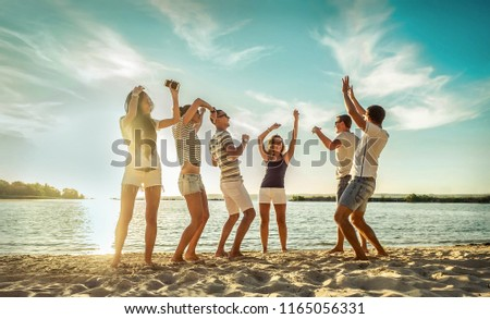 Happy Friends in funny dance on the beach under sunset sunlight in summer sunny day.