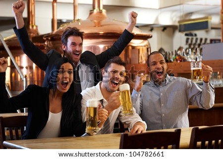 Happy friends in pub watching sport in TV together drinking beer cheering for team and celebrating.