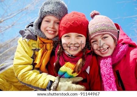 Happy friends in winterwear looking at camera outside