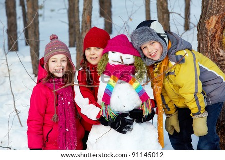 Happy friends in winterwear with snowman looking at camera outside