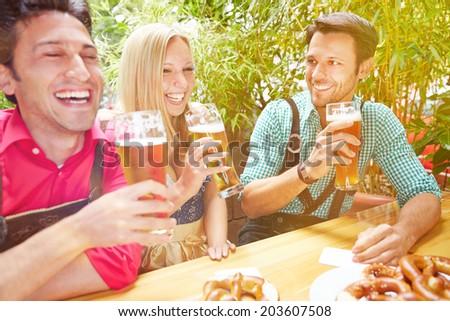 Happy friends laughing in beer garden in Bavaria in summer ストックフォト ©