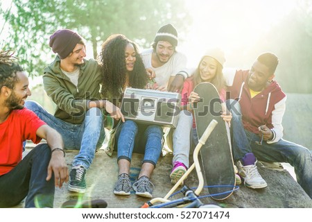 Happy friends listening music and chatting in city park - Young people having fun sitting on skating ramp outdoor - Youth and friendship concept - Focus on afro girl - Warm filter with back sun light