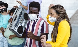 Happy friends listening music with vintage boombox and dancing while wearing face mask outdoor - Multiracial young people having fun during corona virus outbreak - Youth millennial friendship concept