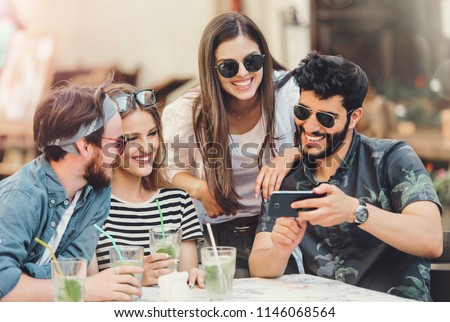 Happy friends looking something in the smartphone and enjoying time together at the summer cafe