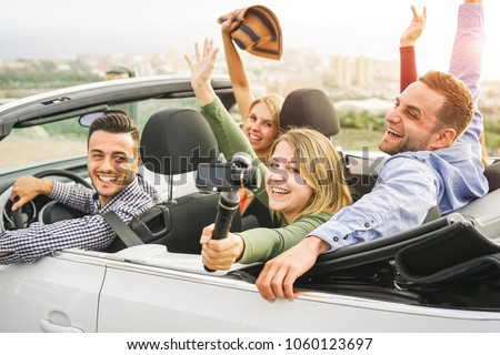 Happy friends making a video with action camera gimbal in convertible car in vacation - Young people having fun in cabriolet auto during their road trip - Friendship, travel, youth lifestyle concept