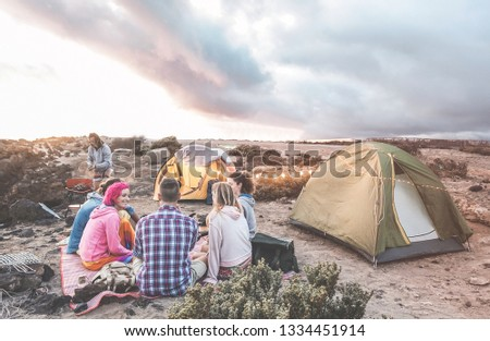 Happy friends making barbecue picnic camping in the desert at sunset - Young people having fun preparing dinner - Travel, tour adventure on nature, vacation and friendship concept