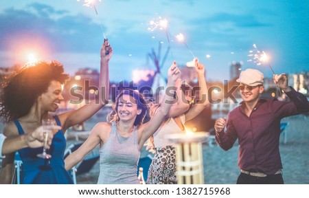 Happy friends making evening beach party outdoor with fireworks - Young people having fun dancing and drinking champagne - Soft focus on center woman hand - Vacation and nightlife concept #1382715968