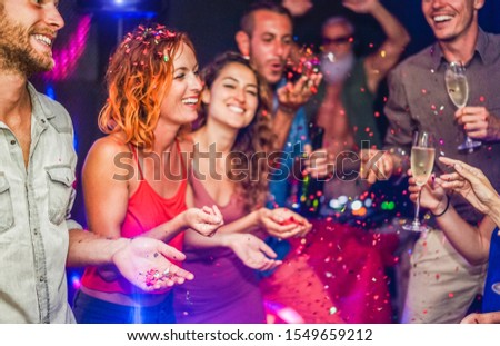 Happy friends making party throwing confetti, dancing and drinking champagne with dj mixing music - Entertainment, fun, new year's eve, nightlife, concept - Focus on blond man hand #1549659212