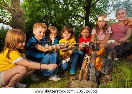 Happy friends near bonfire with marshmallow