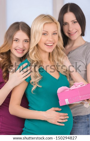 Happy friends on Baby Shower. Beautiful pregnant woman standing close to her friends and smiling at camera