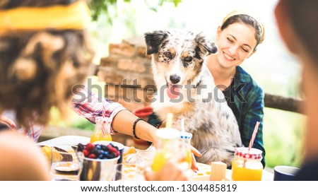 Happy friends on healthy pic nic breakfast at countryside farm house - Young people millennials with cute dog having fun together outdoors at garden party - Food and beverage lifestyle concept