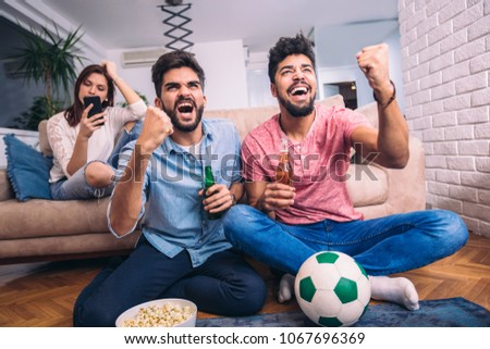 Happy friends or football fans watching soccer on tv and celebrating victory at home.Friendship, sports and entertainment concept. - Shutterstock ID 1067696369
