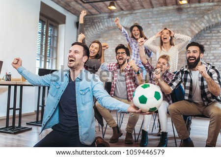 Happy friends or football fans watching soccer on tv and celebrating victory. Friendship, sports and entertainment concept. #1059446579