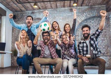 Happy friends or football fans watching soccer on tv and celebrating victory. Friendship, sports and entertainment concept.