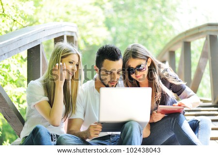 Happy friends outdoor with laptop