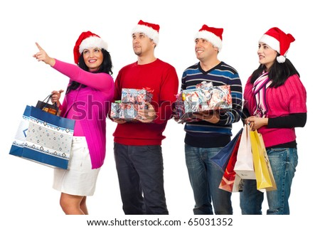 Happy friends people at shopping for Christmas,one of woman pointing up and showing something to her friends isolated on white background