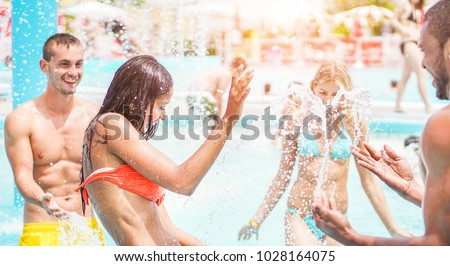 Happy friends playing in swimming pool party - Young diverse culture people having fun on summer vacation - Focus on latin woman face - Youth lifestyle, travel, holidays and friendship concept
