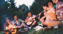Happy friends playing music and enjoying bonfire in nature
