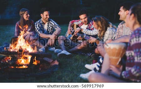 Shutterstock Happy friends playing music and enjoying bonfire in nature