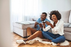 Happy friends playing video games with virtual reality glasses - Young people having fun with new technology console online. Young African American Couple Playing On Game Console With Joysticks